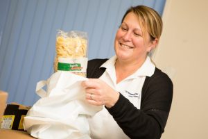 Lady, packing pasta into a shopping bag