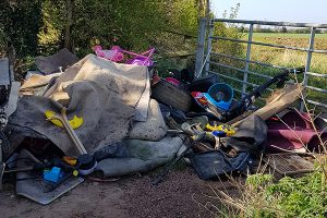 Large pile of Flytipped rubbish at farm gates